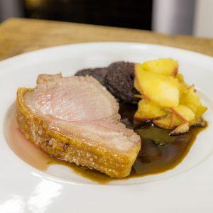 Roast shoulder of pork with black pudding , and caramelised apple sauce